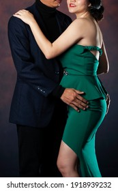 Couple Fashion Portrait, Embracing Man and Sexy Woman in elegant evening dresses. Conceptual portrait of a young couple.
