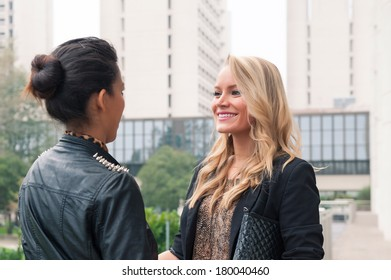 Couple fashion woman portrait outdoors with modern buildings as background.