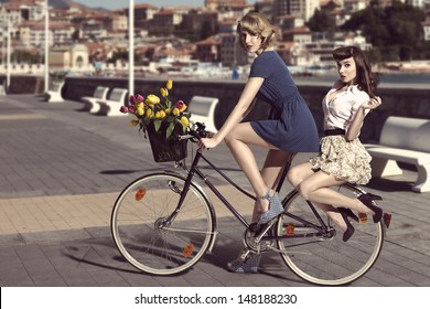 couple of fashion women with vintage style on bicycle, colourful tulips in the basket of the bike in vintage color outdoor near the sea