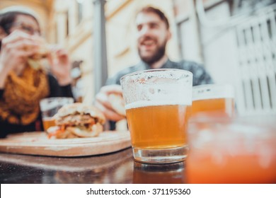 Couple In Fast Food Restaurant Eating Burgers. Focus Is On Glass Of Beer