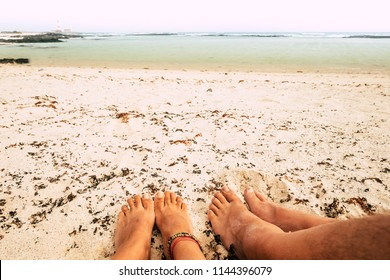 couple of feet relaxing at the beach on the yellow sand, paradise tropical pace of vacation. ocean in background, nudism concept for alternative free leisure activity during holiday