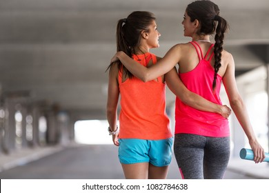 Couple of female friends jogging on the city street under the city road overpass.They relaxing after jogging and making fun.Embracing each other.Rear view.