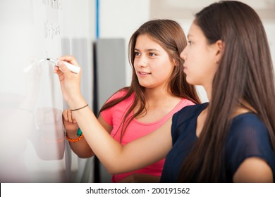Couple of female high school students writing on a white board during class