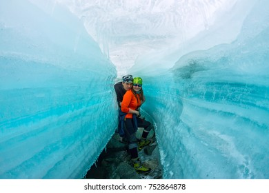 couple female and man inside the crack in the ice glaciers Iceland