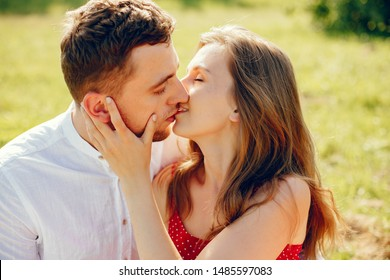Couple in a field. Girl in a red dress. Man in a white shirt