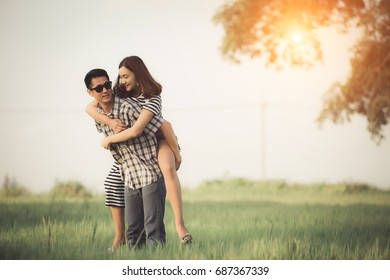 Couple in field at sunset