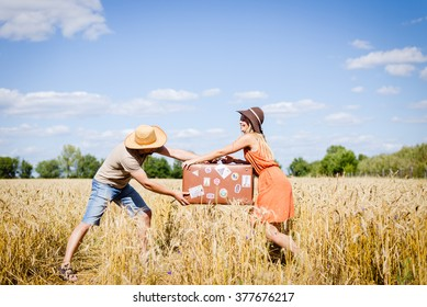 Couple fighting in field holding suitcase on countryside landscape blue sky outdoors background.