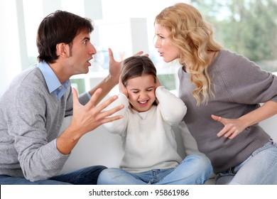 Casal lutando na frente da criança