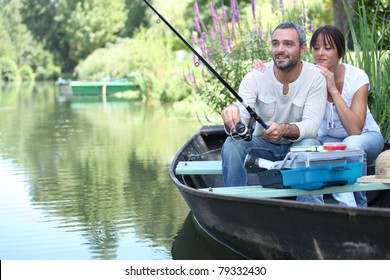 Couple fishing in a small boat on a river