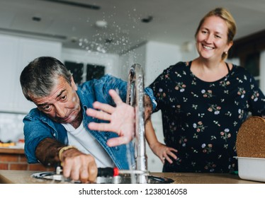 Couple fixing a kitchen sink