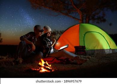 Couple with flashlight reading book near bonfire at night. Camping season