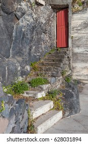 Couple of flight of steps in ruins going up to a red door