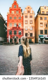 Couple follow holding hands traveling together in Stockholm sightseeing walk  vacations lifestyle Stortorget architecture Sweden landmarks