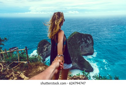 couple follow me in island, Woman wanting her man to follow her in vacation or honeymoon to beach by the ocean, love, hair wild, Indonesia Bali