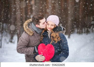 couple in the forest in winter, walk, kiss, hug and hold hands heart