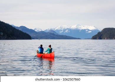 Couple Friends Canoeing On A Wooden Canoe During Sunny Day Taken In Harrison Lake