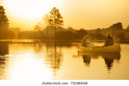 Couple of friends and a dog on a canoe adventure trip on a lake or a river