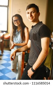 couple friends enjoying in cafe together. Young people meeting in a cafe. Young men and woman standing at bar counter in cafe and smiling