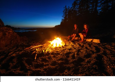 Couple friends are enjoying a camp fire on the beach during a vibrant summer sunset. Taken in Hecht Beach, Northern Vancouver Island Ocean Coast, BC, Canada.