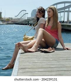Couple of friends girls sitting near the bridge on the sea berth