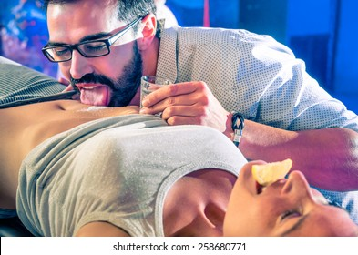 Couple of friends having fun in disco night club with body tequila drink party - Nightlife with crazy game for young people - Vintage look with soft focus on glass and salt with shallow depth of field
