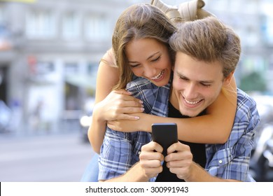 Couple or friends laughing funny and having fun with a smart phone in a big city street