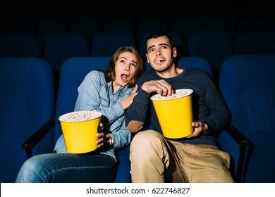 Couple of friends looking horror movie in cinema