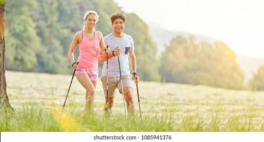 Couple of friends nordic walking in summer with joy in the nature