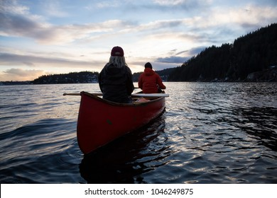 Couple friends on a wooden canoe are paddling in an inlet surrounded by Canadian mountains during a vibrant sunset. Taken in Indian Arm, near Deep Cove, North Vancouver, British Columbia, Canada.