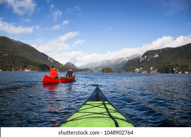 Couple friends on a wooden canoe are paddling in an inlet surrounded by Canadian mountains. Taken in Indian Arm, near Deep Cove, North Vancouver, British Columbia, Canada.