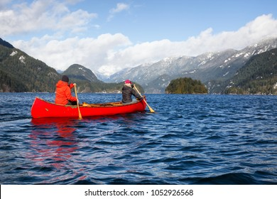 Couple Friends On A Wooden Canoe Are Paddling In An Inlet Surrounded By Canadian Mountains