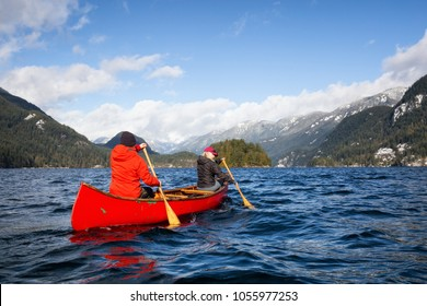 Couple friends on a wooden canoe are paddling in an inlet surrounded by Canadian mountains. Taken in Indian Arm, near Deep Cove, North Vancouver, British Columbia, Canada. Concept: Adventure, explore