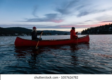 Couple Friends On A Wooden Canoe Are Paddling In An Inlet Surrounded By Canadian Mountains During
