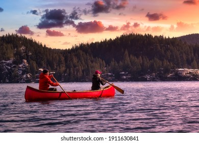 Couple friends on a wooden canoe are paddling in water. Sunset Sky Art Render. Taken in Indian Arm, near Deep Cove, North Vancouver, British Columbia, Canada. Concept: Adventure, Sport, Explore