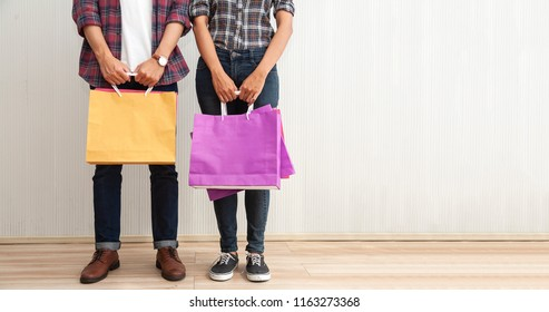 couple or friends with shopping bags while stand together on wall fashion,copy space. summer sale, Black friday super sale and shopping ,consumerism and people concept