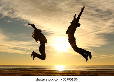 Couple or friends silhouette jumping on the beach at sunset with a warmth light and the sun in the middle