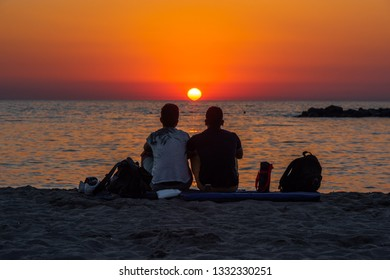 Couple of friends are watching the sunset on the beach