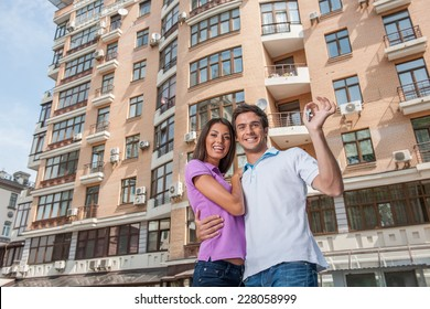 Couple in front of new home holding door keys. man hugging womam and holding apartment keys