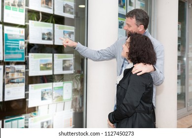 couple in front of the window of a real estate agent