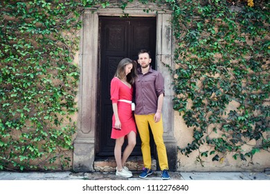 Couple in front of wooden old door and wall covered with ivy