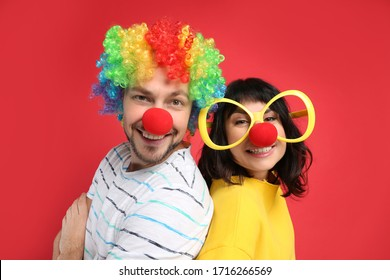 Couple with funny accessories on red background. April fool's day