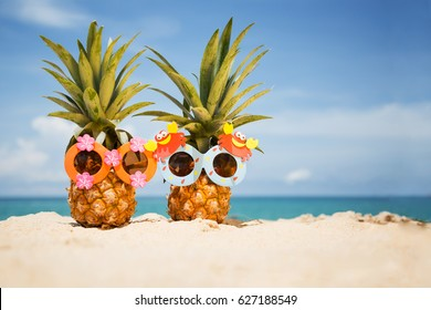 Couple of funny attractive pineapples in children's cheerful sunglasses on sand against turquoise sea. Tropical summer vacation concept. Happy sunny day on the beach of tropical island.