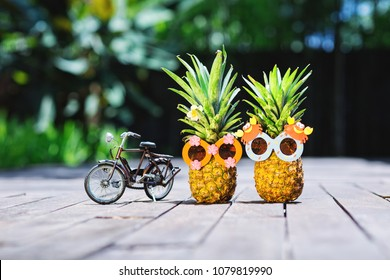 Couple of funny attractive pineapples -cyclists in children's cheerful sunglasses on the road on the tropical island. Tropical summer vacation concept. Cycling. Happy sunny day on bicycle