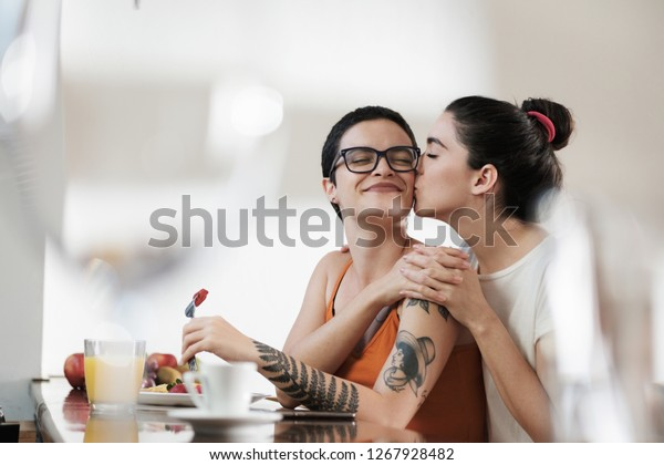 A couple of gay woman having breakfast together and holding hands while smiling and kissing. Same sex young married female couple in their daily routine at a morning showing some affection LGBT