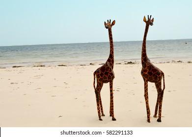 Couple of giraffes carving exposed on the white sandy beach of Bamburi in Mombasa, Kenya