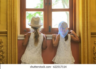 couple of girl curious looking something out of the window