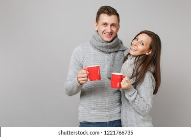 Couple girl guy in gray sweaters, scarves hold cups with tea isolated on grey wall background, studio portrait. Healthy lifestyle, ill sick disease treatment, cold season concept. Mock up copy space