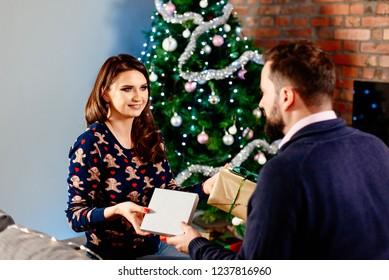 Couple giving Christmas presents. Christmas surprise. Family at Christmas