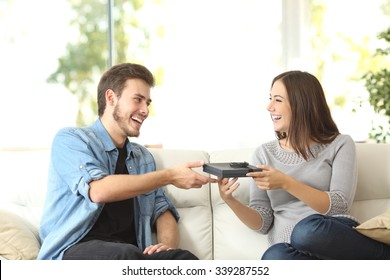 Couple giving or receiving a gift for birthday or anniversary at home