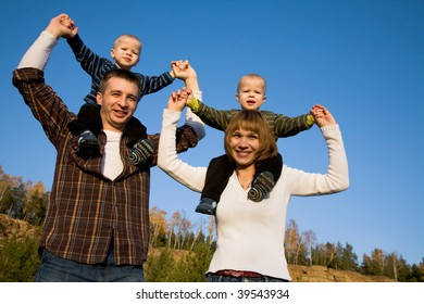 Couple giving two young sons of twins on their shoulders against the blue sky